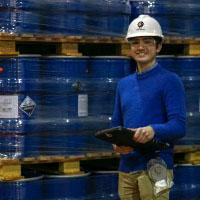 A man in a white hard hat and bright blue shirt holds a clipboard in front of 10 gallon drums.