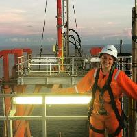 In a smaller version of the top photo, a woman wearing a hard hat and orange jumpsuit stands on the deck of a ship