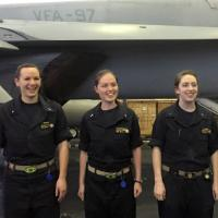Three women in black jumpsuits stand in front of an aircraft below the decks of an aircraft carrier