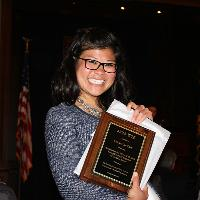A woman grins at the camera holding a plaque