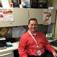 Scott Bemis in his office, wearing a red shirt and white lanyard
