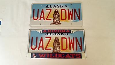 """Two Alaska license plates, with """"UAZ"""" on one side of a bear illustration and """"DWN"""" on the other"""