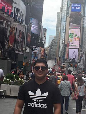A man in black sunglasses and a black shirt standing in the middle of Times Square