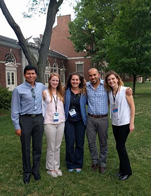 A group of people wearing conference lanyards in front of a tree next to a red brick building on a college campus