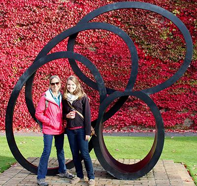 Two women stand in front of a sculpture composed of overlapping circles with a wall of red ivy behind them