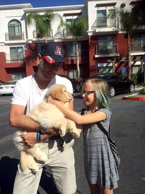 A man wearing a UA baseball cap holds a small fluffy labrador puppy, while a young girl with blue stripes in her hair pets the dog's face.