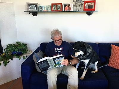 A man in a blue UA shirt sits on a blue couch next to a large black and white dog. He appears to be reading aloud to the dog from a book.