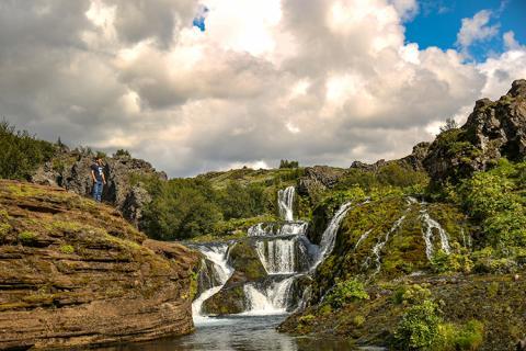 A man stands overlooking gentle waterfalls cascading down a mountainside