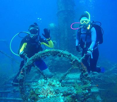 A pair of scuba divers waving in front a sea wreck