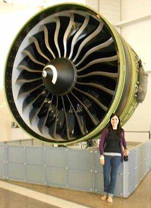 A woman stands in front of an enormous turbine at least twice as tall as she is
