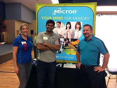 """Two men and a woman standing in front of a poster that says """"Micron: Your Mind. Our Memory."""""""