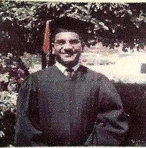A man wearing a cap and gown standing before some bushes