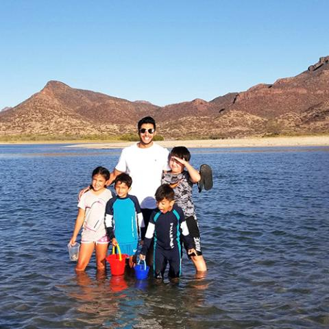 A man and four children wading in water with mountains in the background