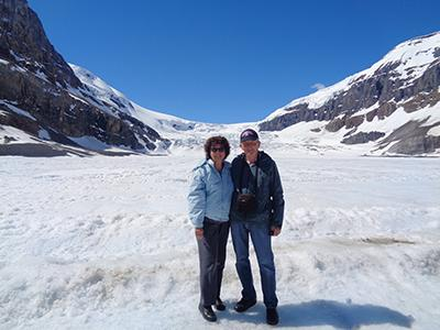 A woman and a man in winter gear on top of a snow-covered glacier