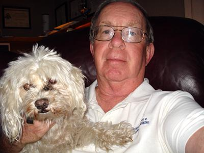A man with wire-rimmed glasses holds a fluffy white dog