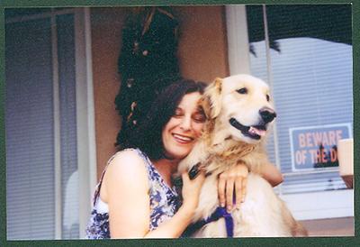An older photo of a woman with dark hair hugging a Golden Retriever.