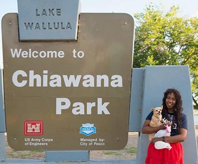"A woman wearing a red skirt and blue UA shirt holding a small yellow dog stands in front of a ""Welcome to Chiawana Park"" sign"