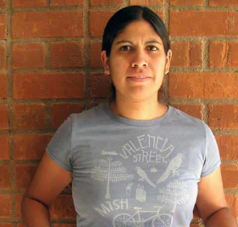 A woman wearing a gray T-shirt and standing before a brick wall.