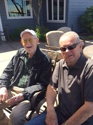Two men in patio chairs, outside on a sunny day