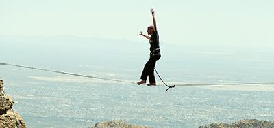 A man walks a tightrope at Windy Point in the Catalina Mountains