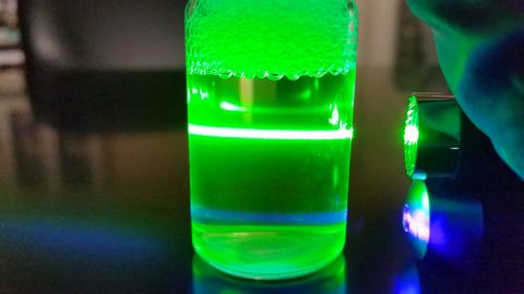 A green laser illuminates a beaker full of clear liquid