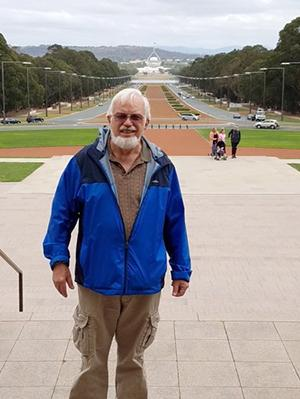 A man with a bushy white beard wearing a blue jacket stands in front of an expansive promenade