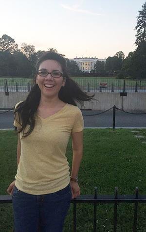 A woman with long hair wearing a yellow shirt stands in front of the White House in Washington, D.C.