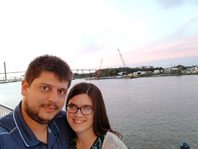 A man and woman stand by a riverfront with a bridge in the background