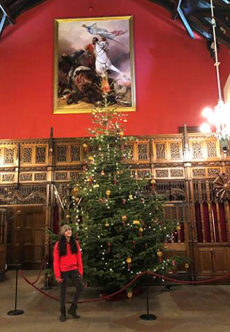 A woman standing before a Christmas tree and a painting in a castle room