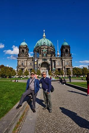 Two men in front of a large palace with green accents
