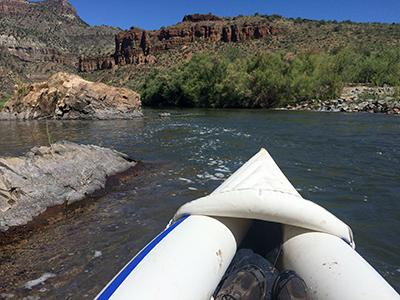 The front of a white kayak with water and a canyon in the background