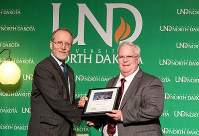 A smaller version of the photo above, wherein a man accepts a framed certificate from another man in front of a University of North Dakota backdrop.