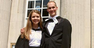A female student and a male student dressed in graduation gowns standing side-by-side before a window