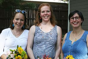 Three young smiling women hold bright yellow flowers in front of their pregnant stomachs.