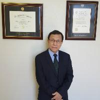A man in a black suit and wire-rimmed glasses stands in front of two framed diplomas