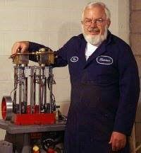 A man with a white beard wearing a shop jumpsuit stands in front of a handbuilt boiler