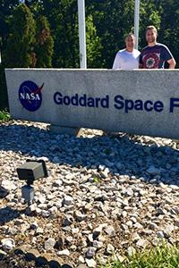 A younger man stands with his father behind a Goddard Space Flight Center entrance sign with the NASA logo