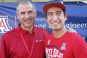 A closer crop of the top photo, in which two mean wearing red UA shirts smile in front of a College of Engineering banner