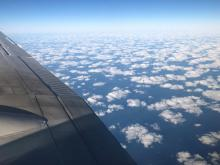 A layer of clouds, as seen from above the wing of a plane.