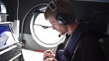 Joe Schlosser takes notes aboard a plane