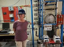 Linda Headly Repking in front of distillation column