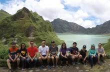 A group of student sitting before a lake that is surrounded by lush green hills.