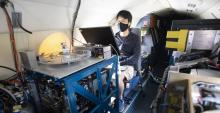 A young man wearing a face masks sits behind a monitor on an airplane, surrounded by technology.