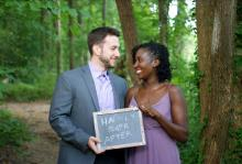 "A man and a woman standing in a forest, looking at each other and smiling while they hold a small chalk tablet that reads ""happily ever after"""
