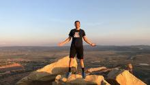 A man in a University of Arizona T-shirt stands on top of a rocky hilltop looking over a flat vista