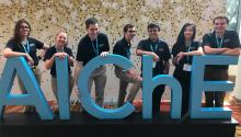 """Seven students in blue polo shirts stand behind cut-out letters spelling """"AIChE"""""""