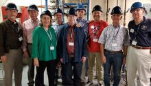 Eight men and one woman stand a laboratory with pipes visible behind them. They are wearing hard hats and lanyards.