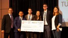 A group of people in business suits stand on a stage holding a large check.