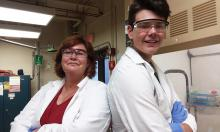 A woman and a young man in lab coats and protective eyewear stand in a chemistry lab with their backs against one another.