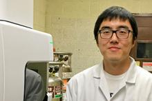 Paper co-author Chao Zeng, a UA doctoral student in chemical engineering, stands by analytical equipment used in the nanoparticle study.
